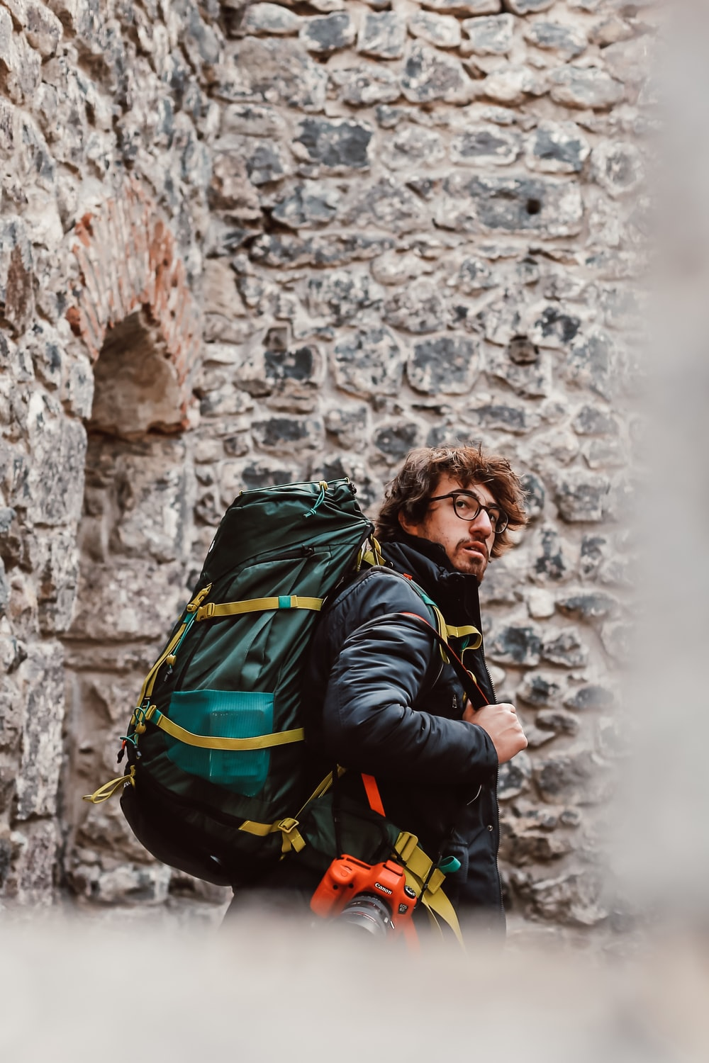 man in black jacket carrying green backpack