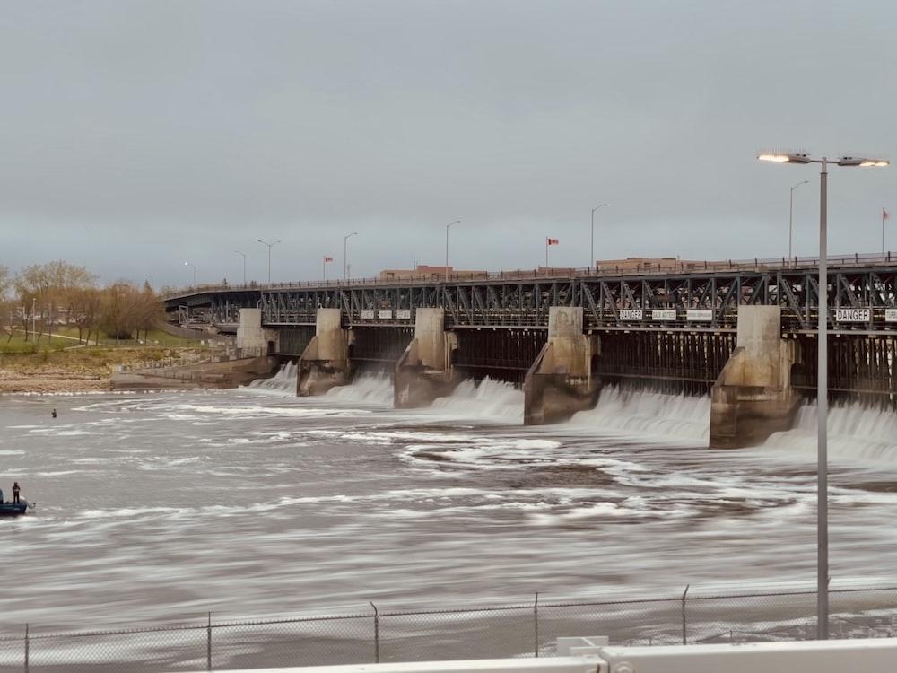 white water dam under white sky during daytime