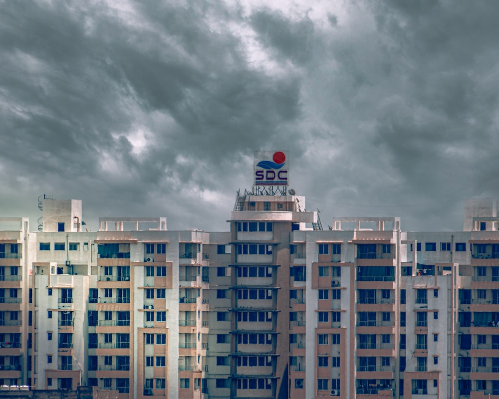 white and blue concrete building under gray clouds during daytime