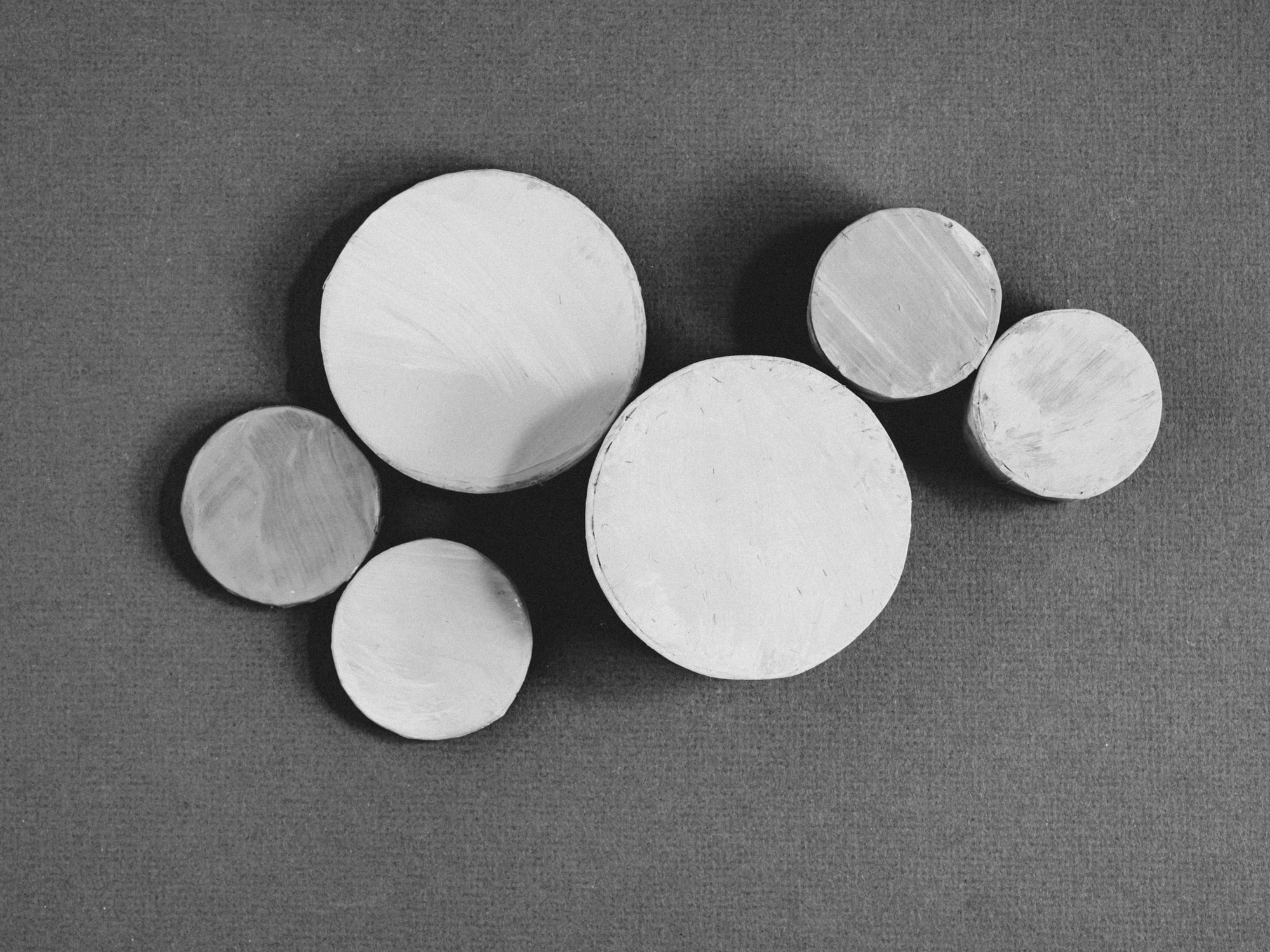 Painted round boxes on a plain paper background.