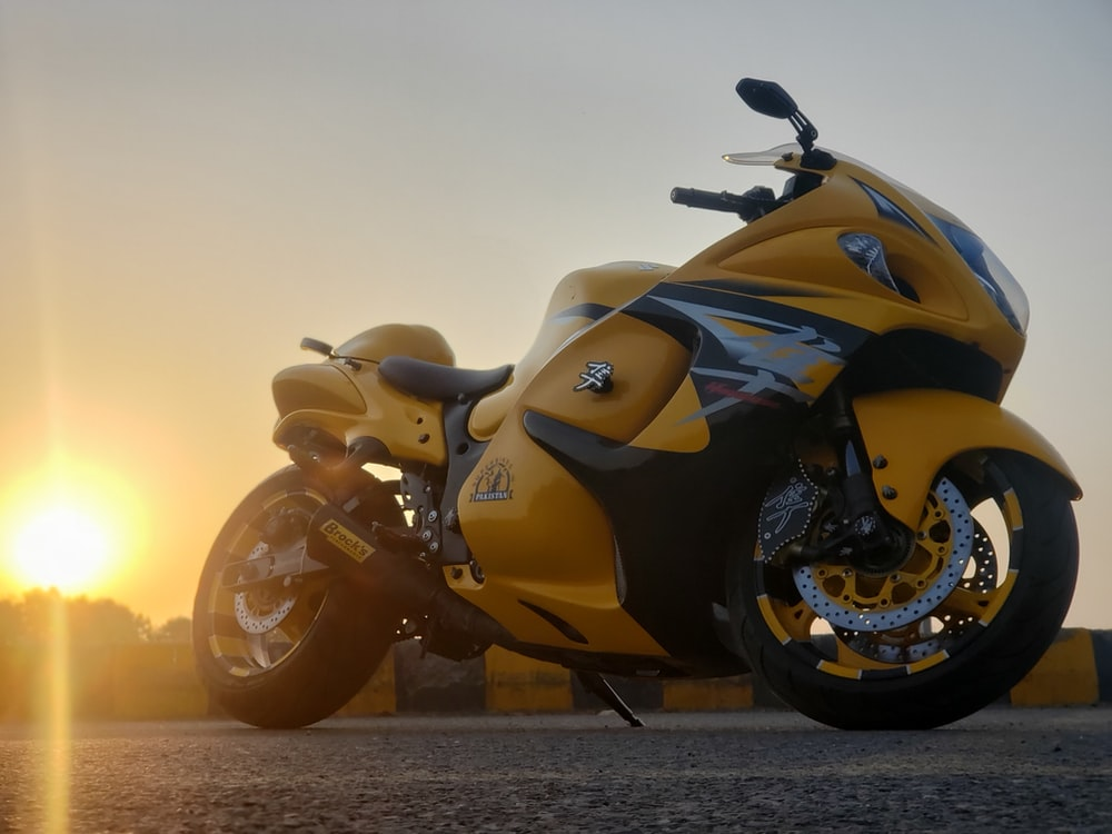 yellow and black sports bike on brown sand during sunset