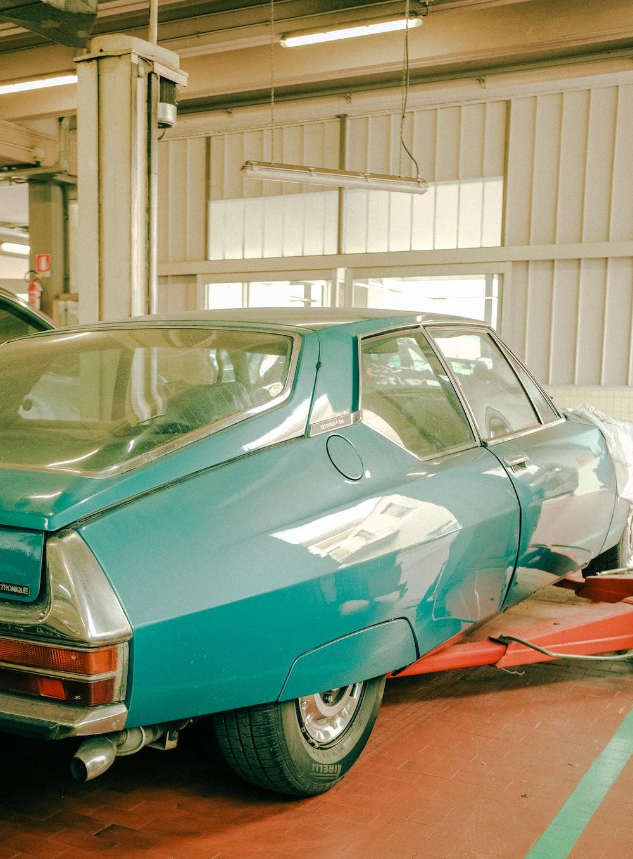 teal car parked in garage