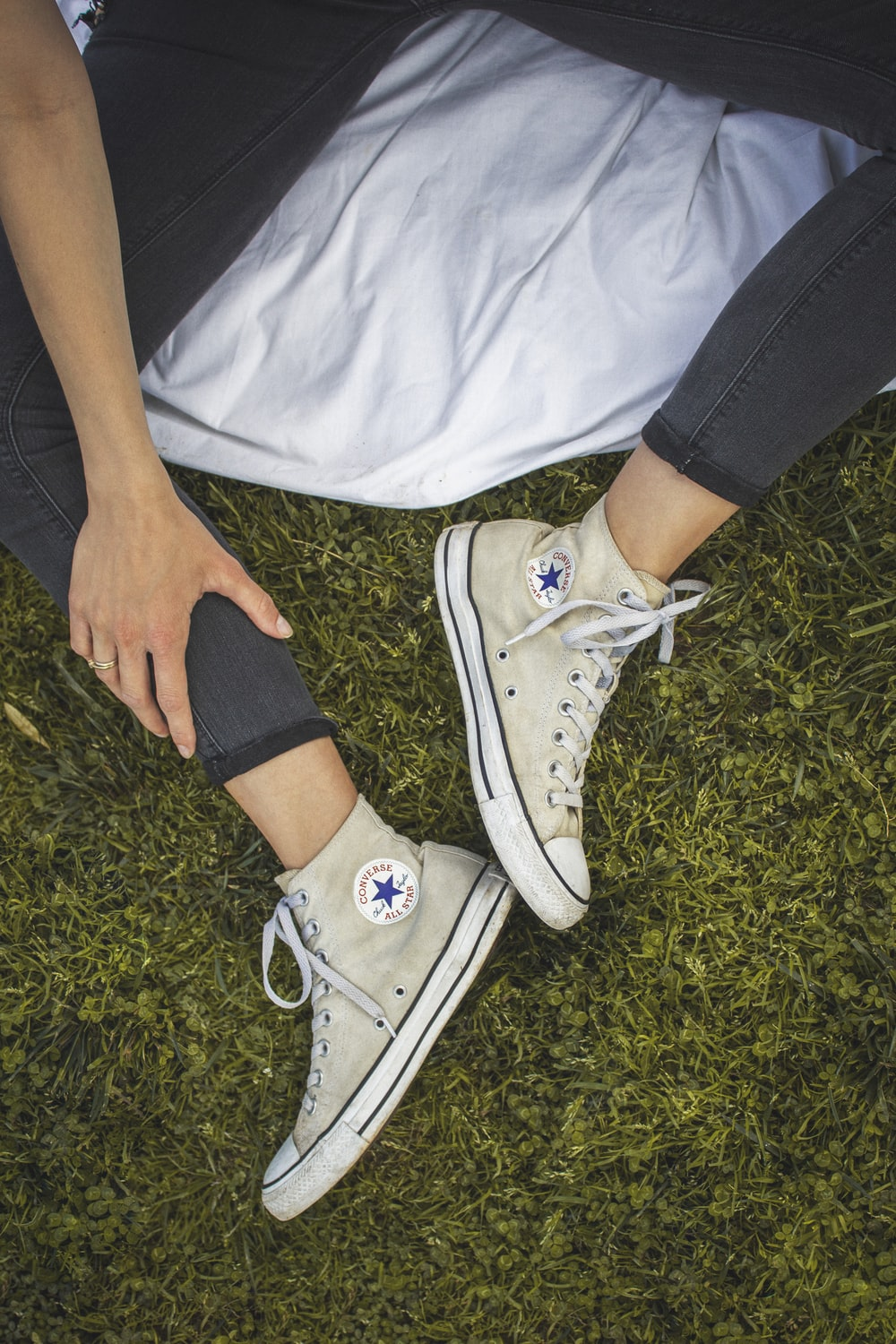 person wearing white converse all star low top sneakers