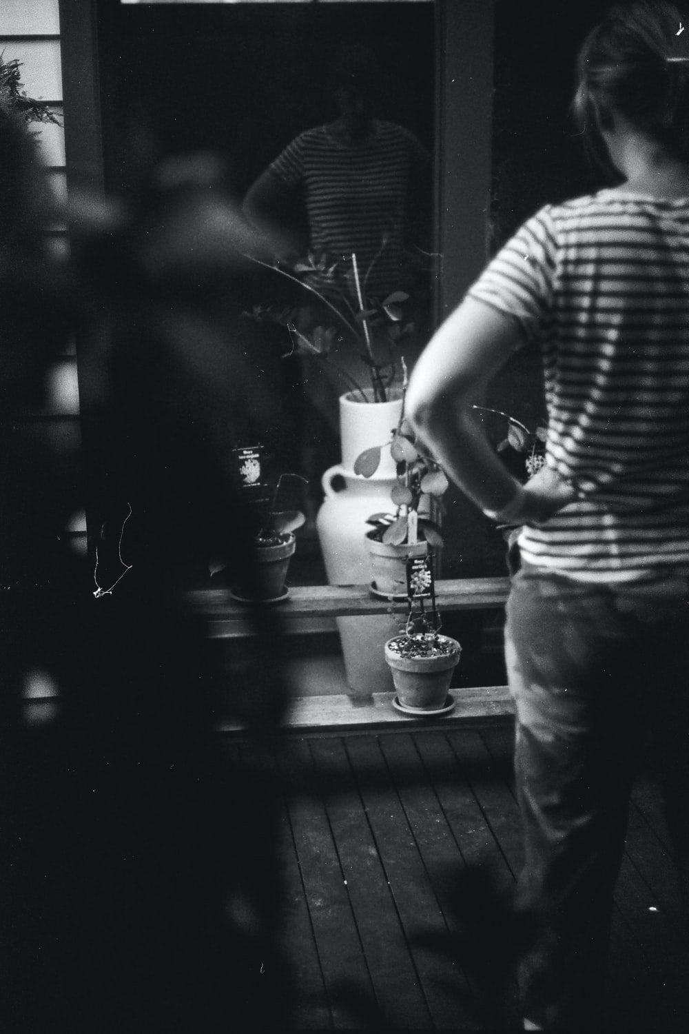 man in stripe shirt and black pants standing in front of window