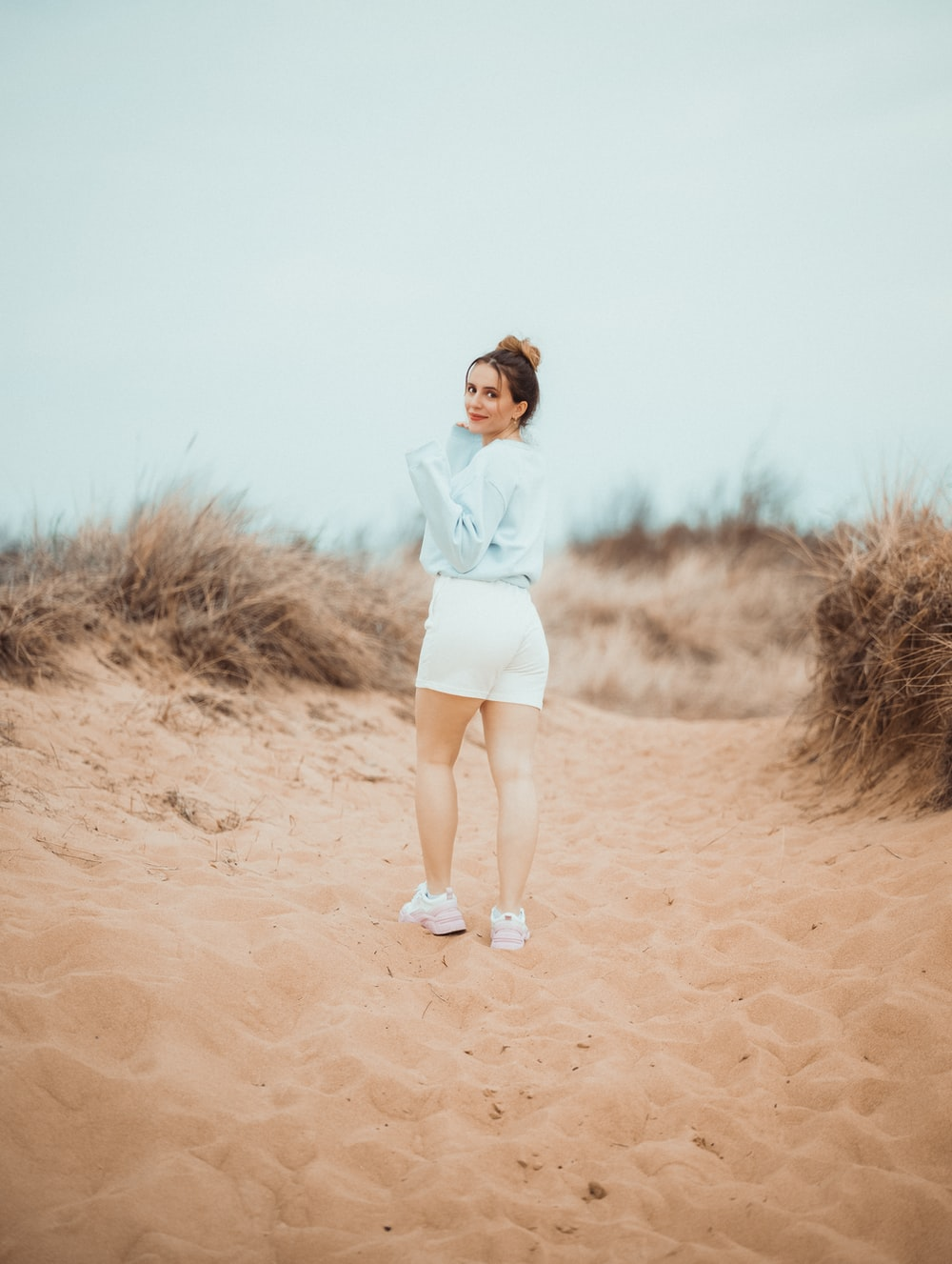 woman in white long sleeve shirt and white shorts standing on brown sand during daytime