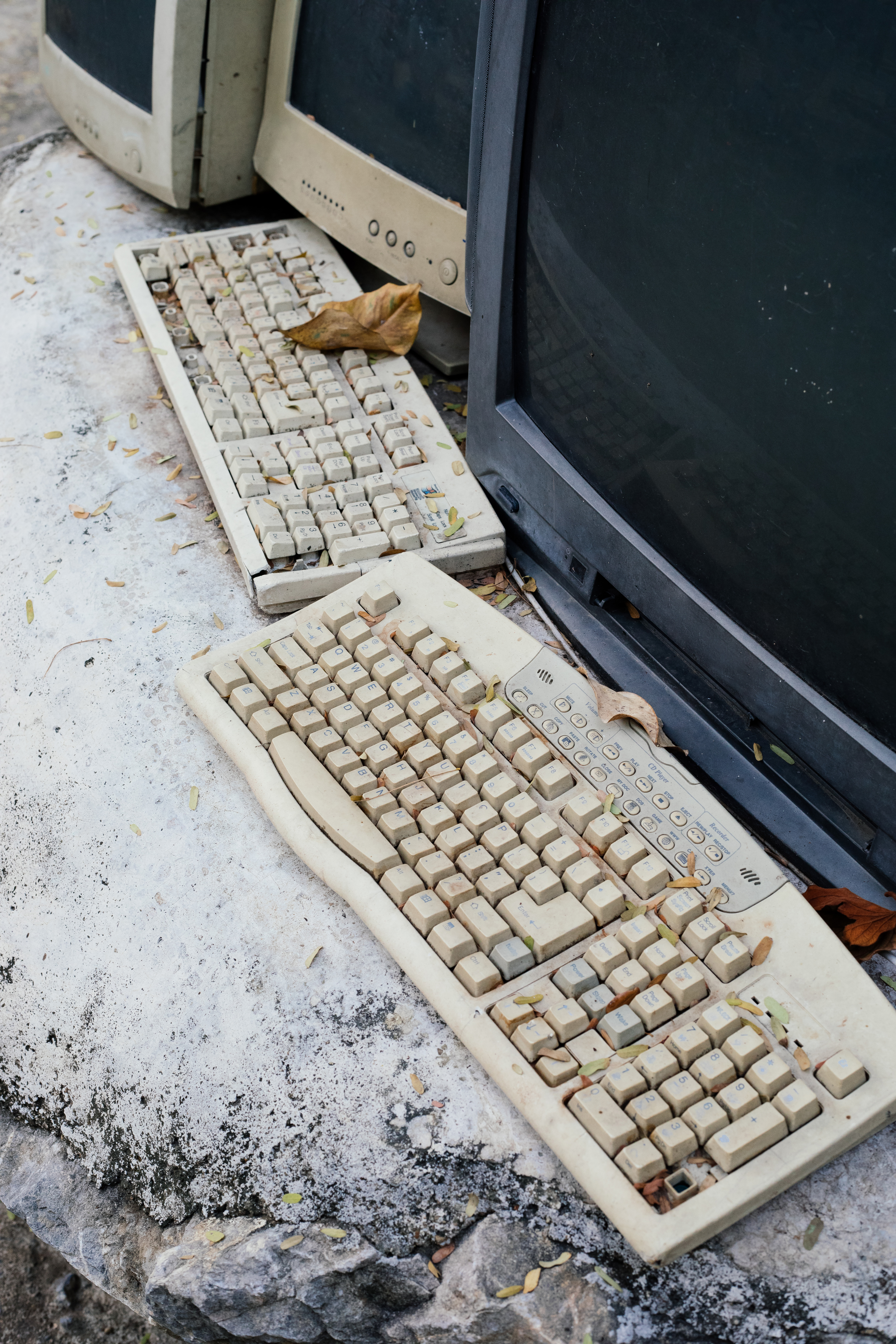 Broken keyboards and monitors on top of stone in a technology graveyard.