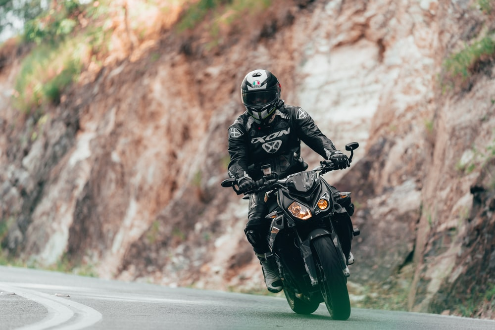 man in black jacket and helmet riding motorcycle on road during daytime
