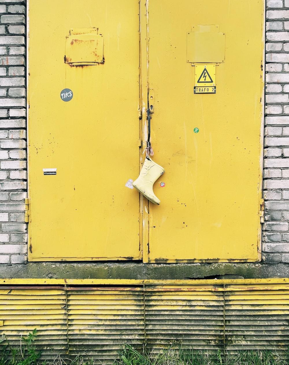 yellow wooden door with white plastic bag