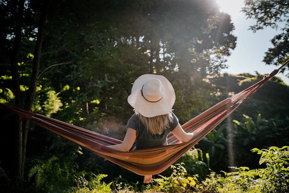 woman in white sun hat sitting on brown wooden bench