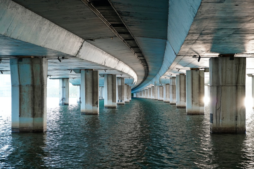 white and brown concrete bridge over body of water during daytime
