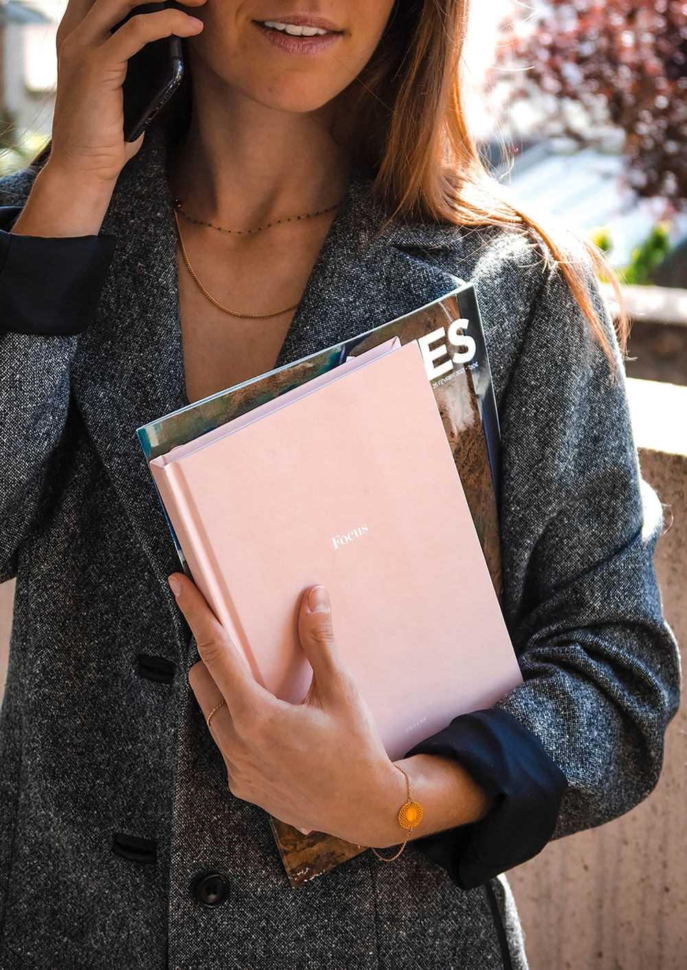 woman in gray cardigan holding white book