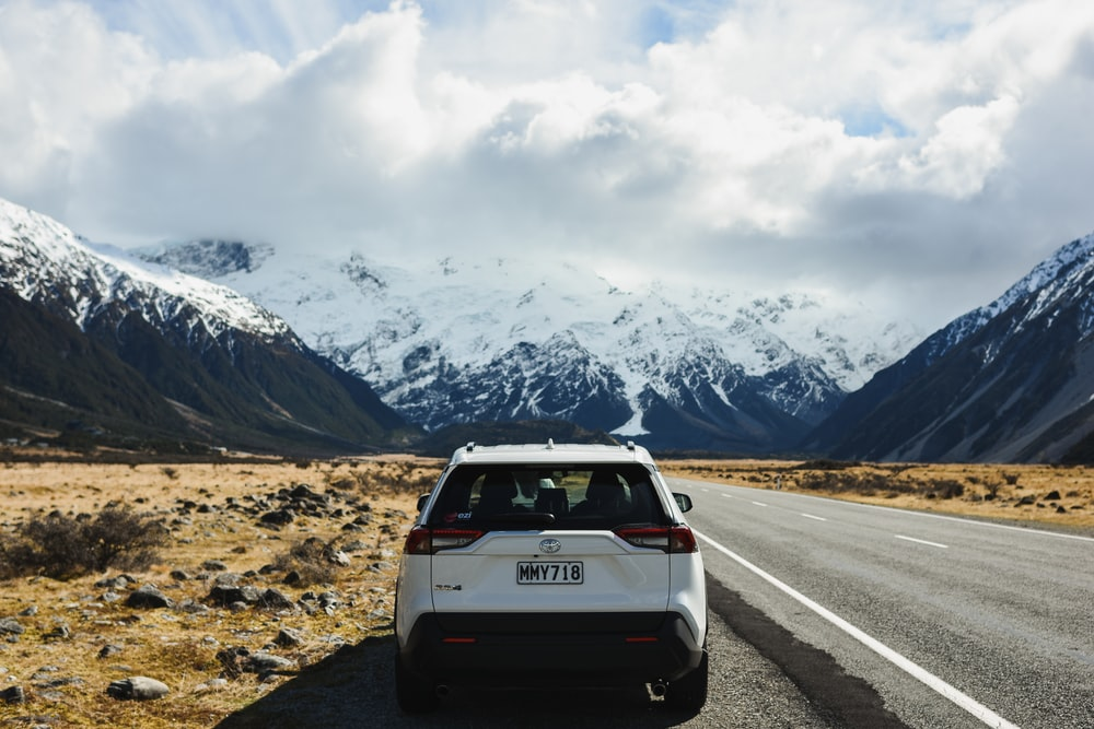 white suv on road near snow covered mountain during daytime