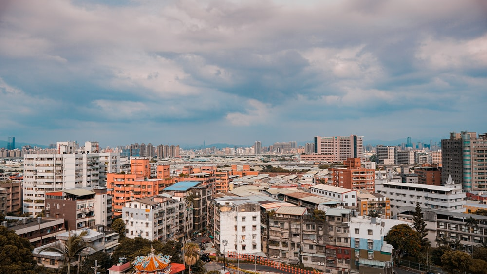 city buildings under white clouds during daytime