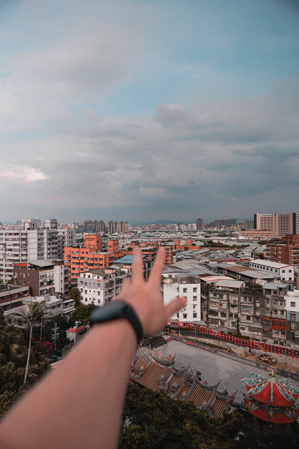 person wearing black watch and black strap watch pointing at city buildings during daytime