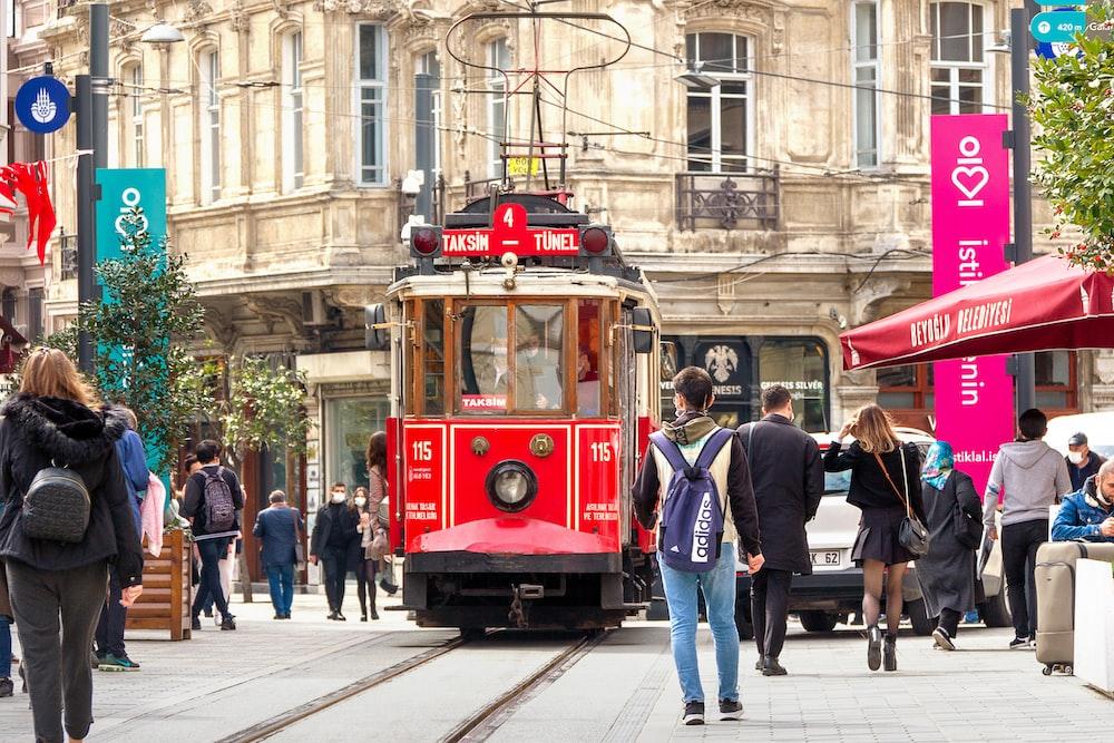 people walking on sidewalk near red tram during daytime