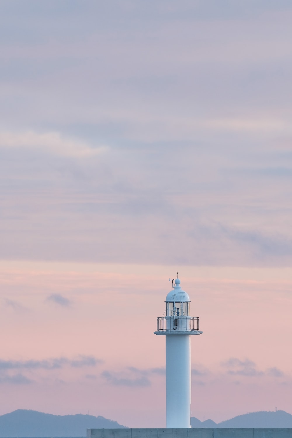 white and black lighthouse under white clouds during daytime