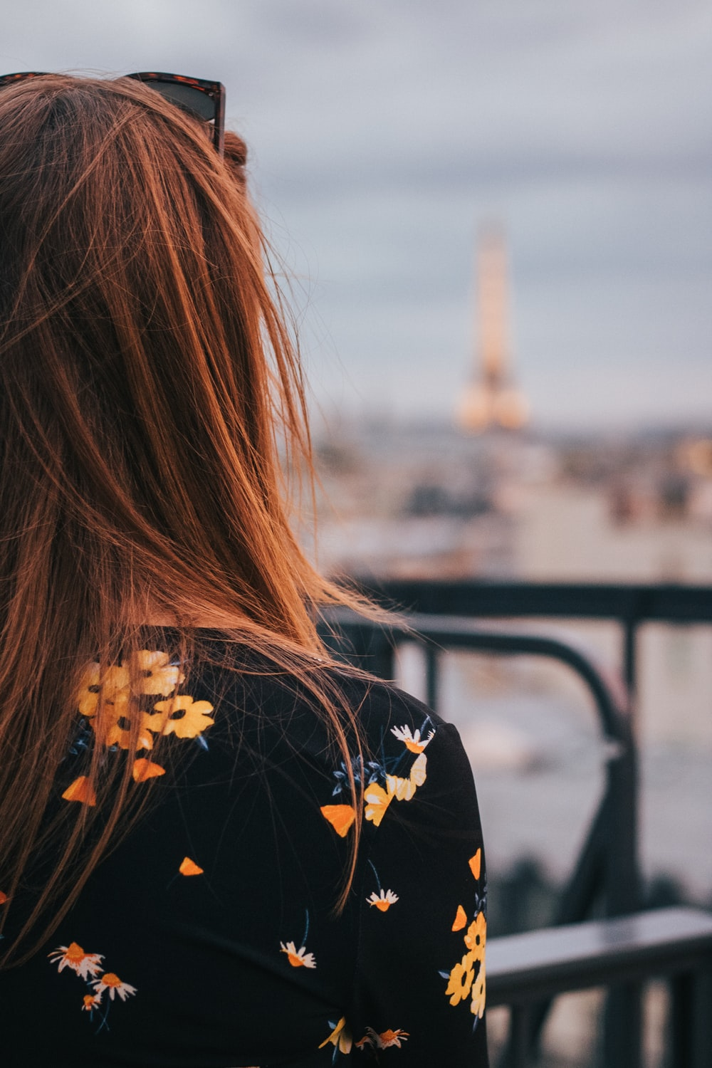 woman in black and yellow floral shirt standing near railings during daytime