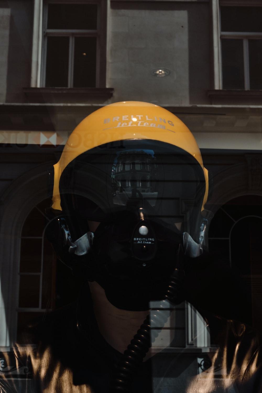 person wearing yellow helmet and black helmet