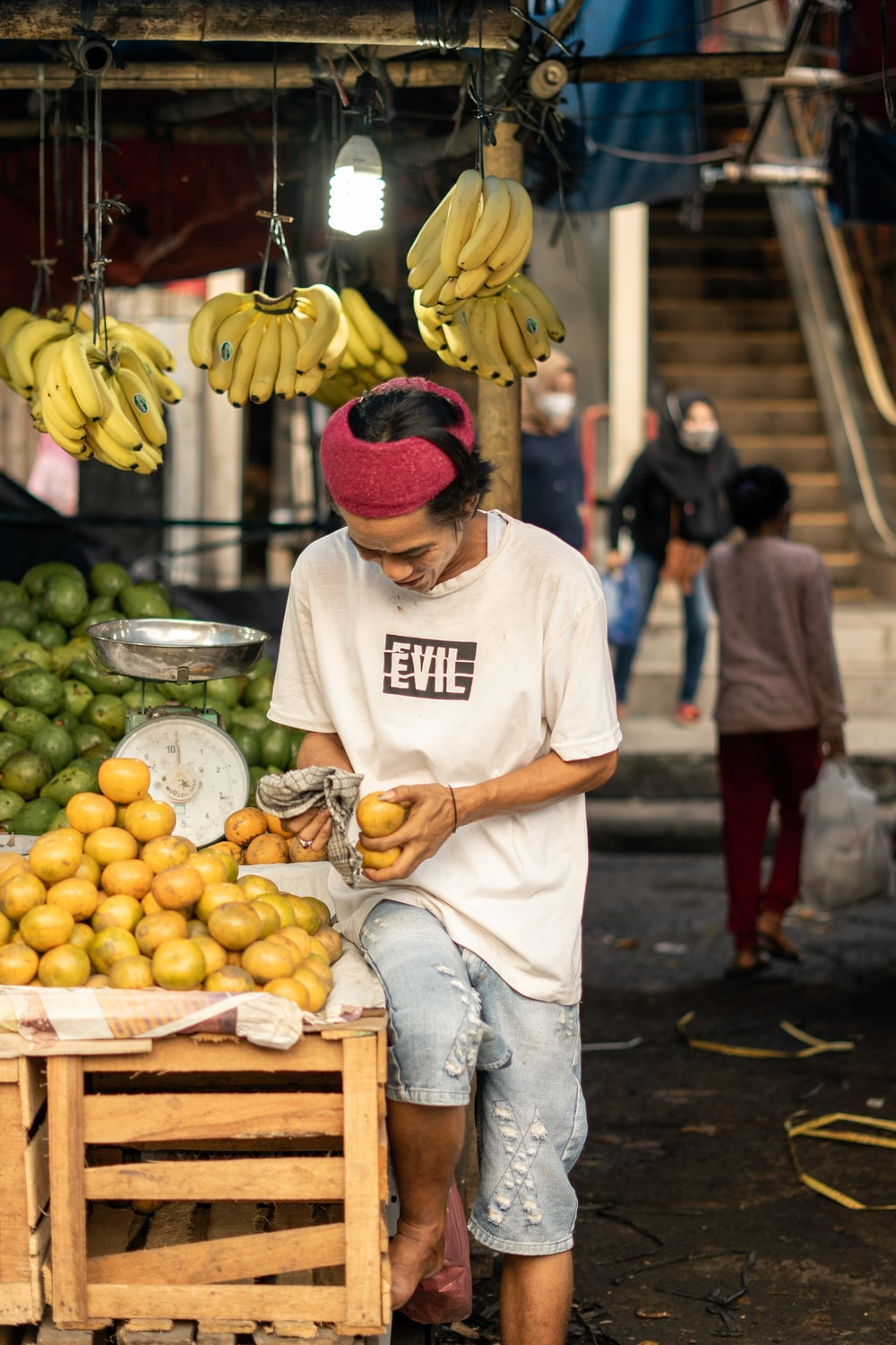 man in white shirt and red knit cap holding yellow banana fruit
