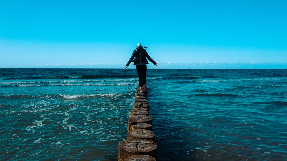 woman in black dress standing on brown wooden dock during daytime