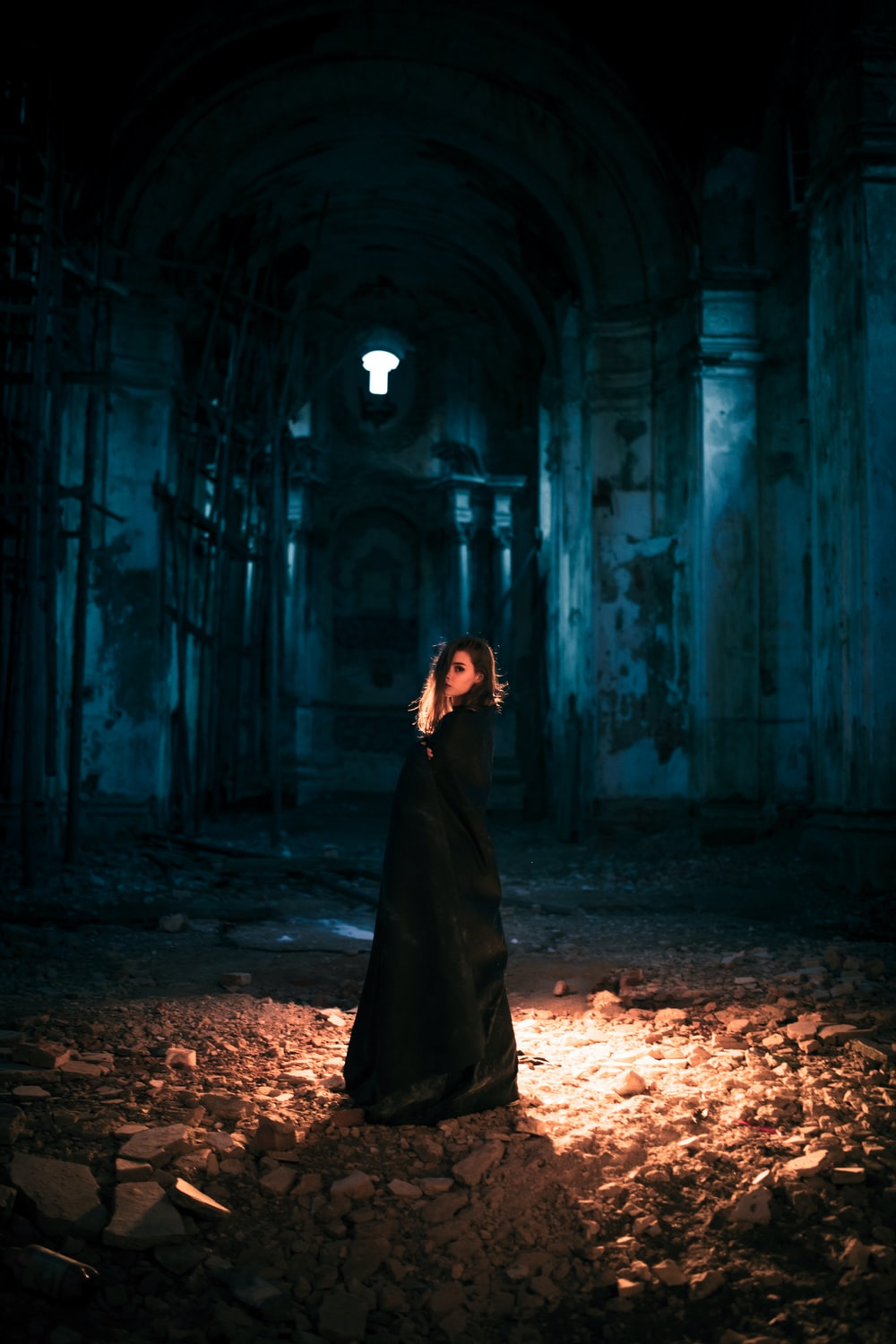 woman in black dress standing in the middle of a tunnel