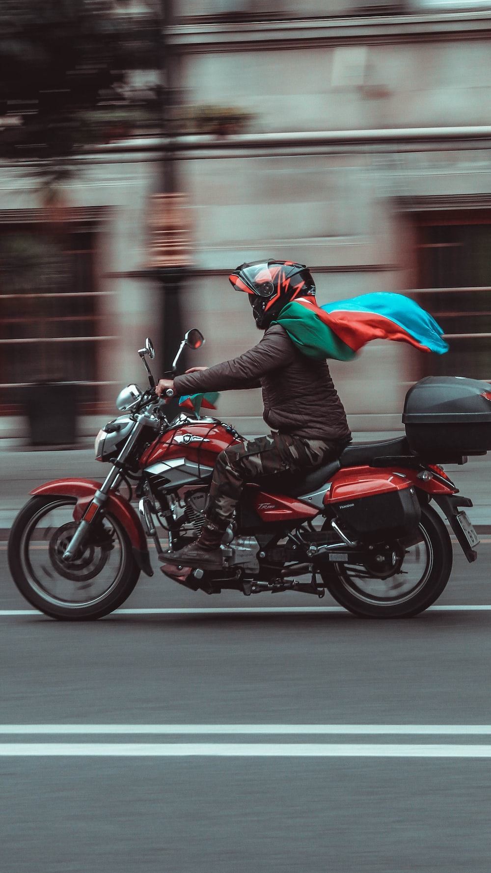 man in black leather jacket riding red and black sports bike