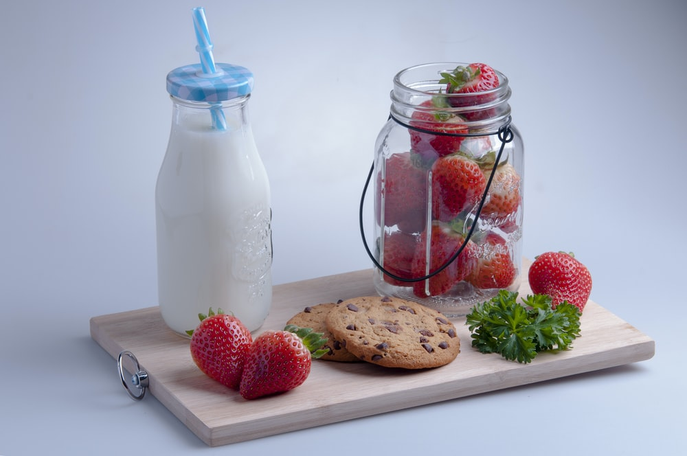 strawberries and blue straw in clear glass jar
