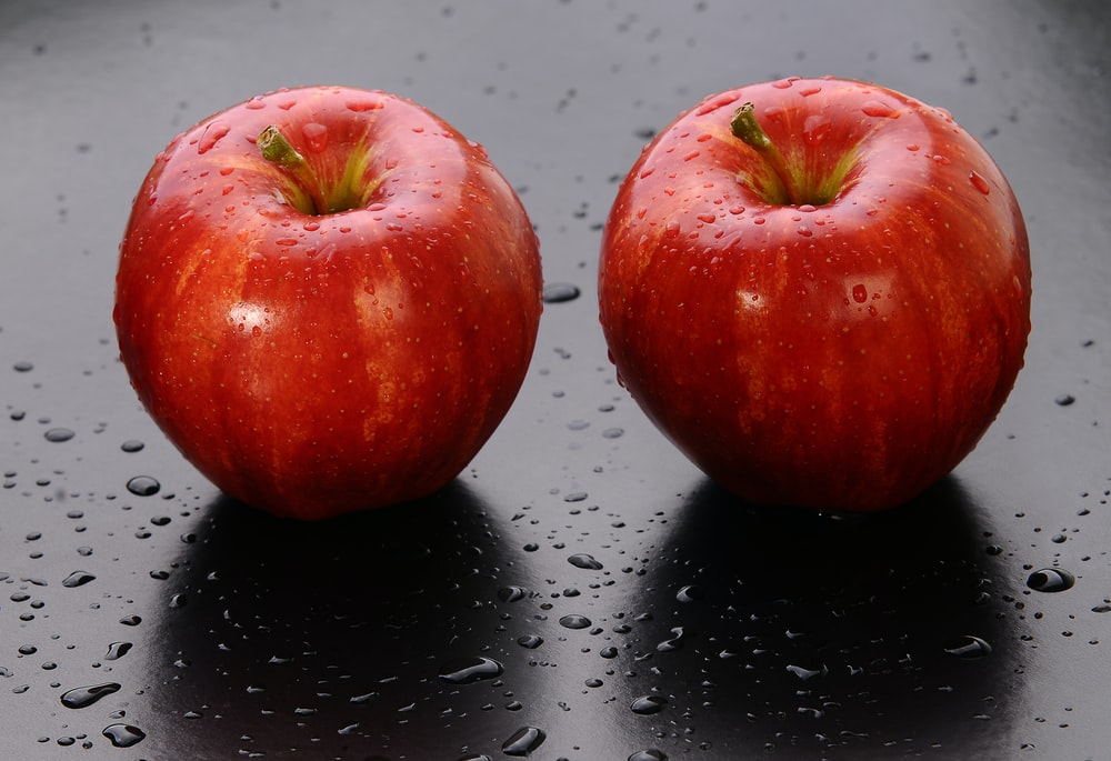 2 red apples on black surface