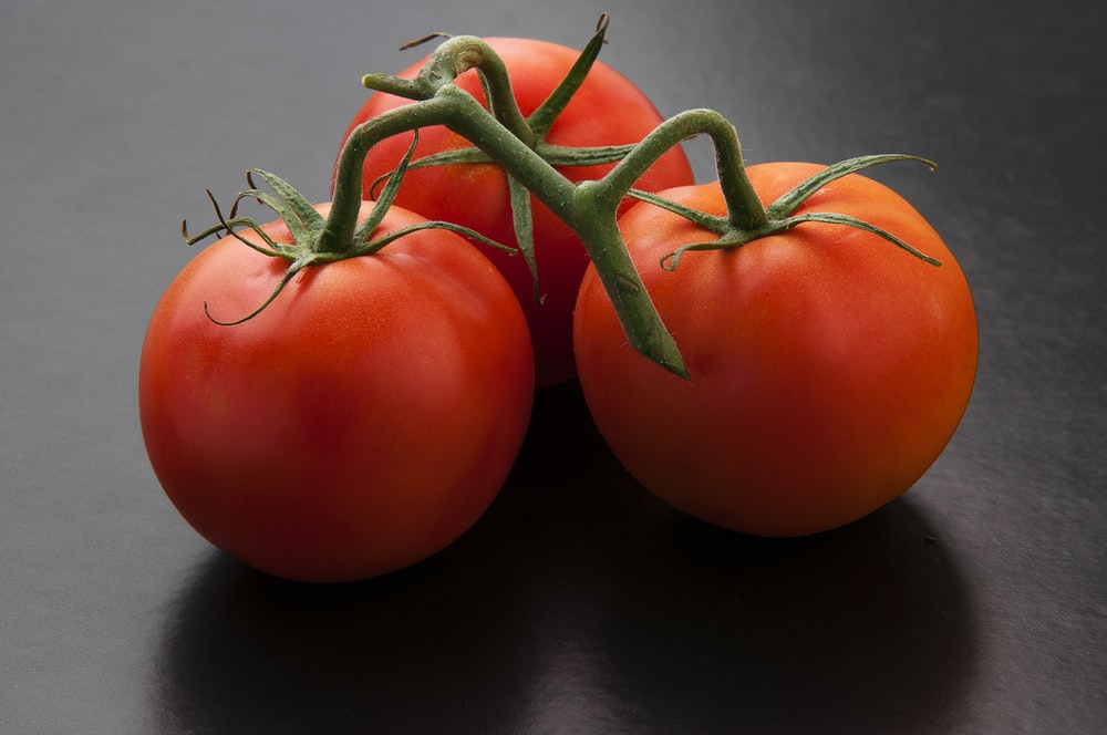 3 red tomato on black table