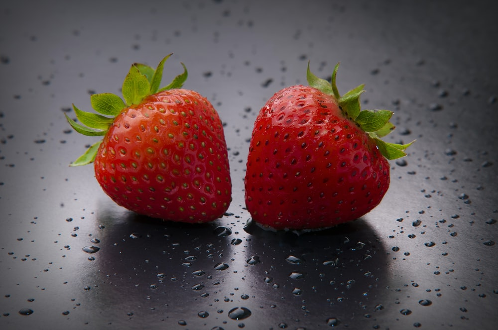 red strawberry on white surface