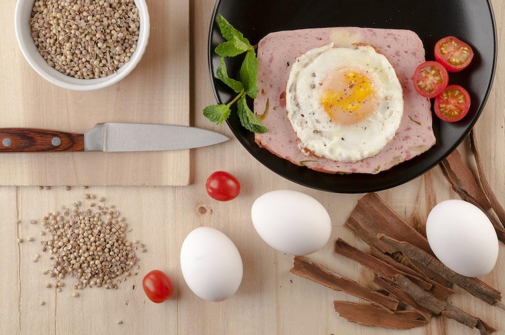 egg on black ceramic bowl beside stainless steel knife
