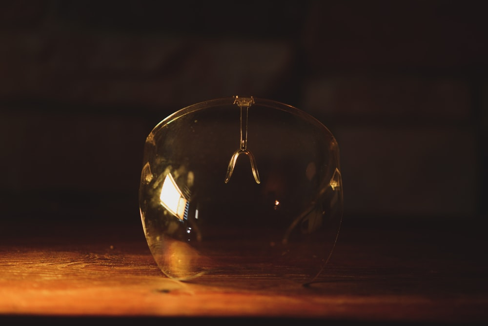 clear glass ball on brown wooden table