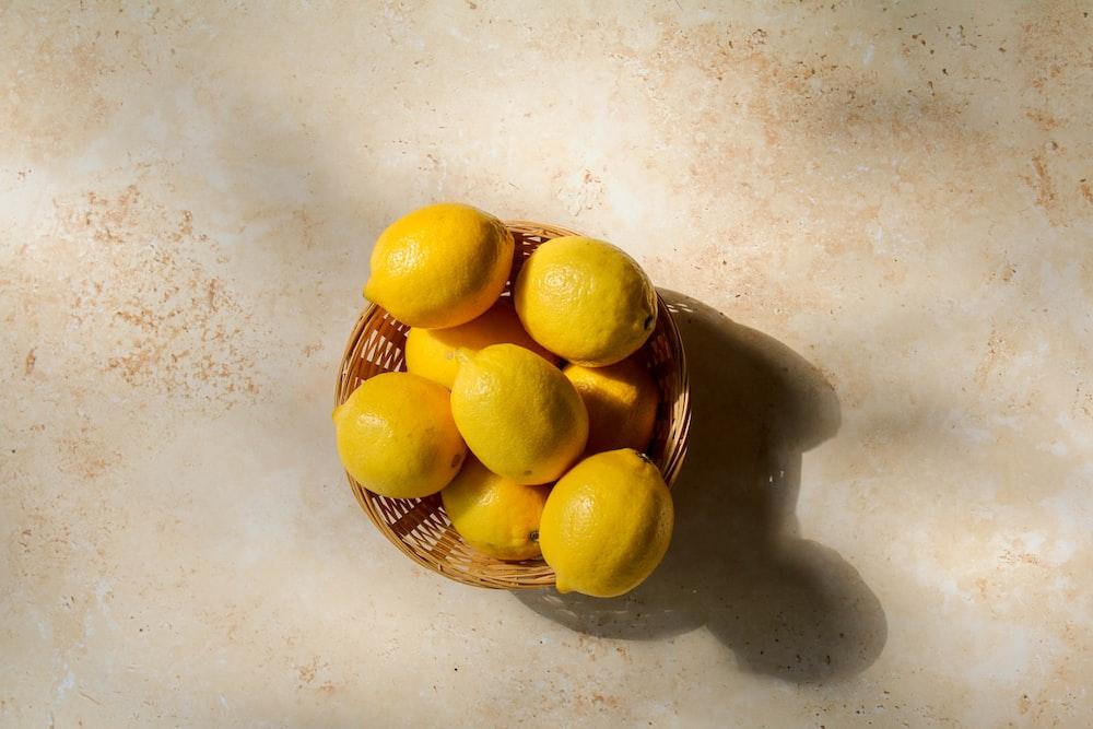 yellow lemon fruits on brown woven basket