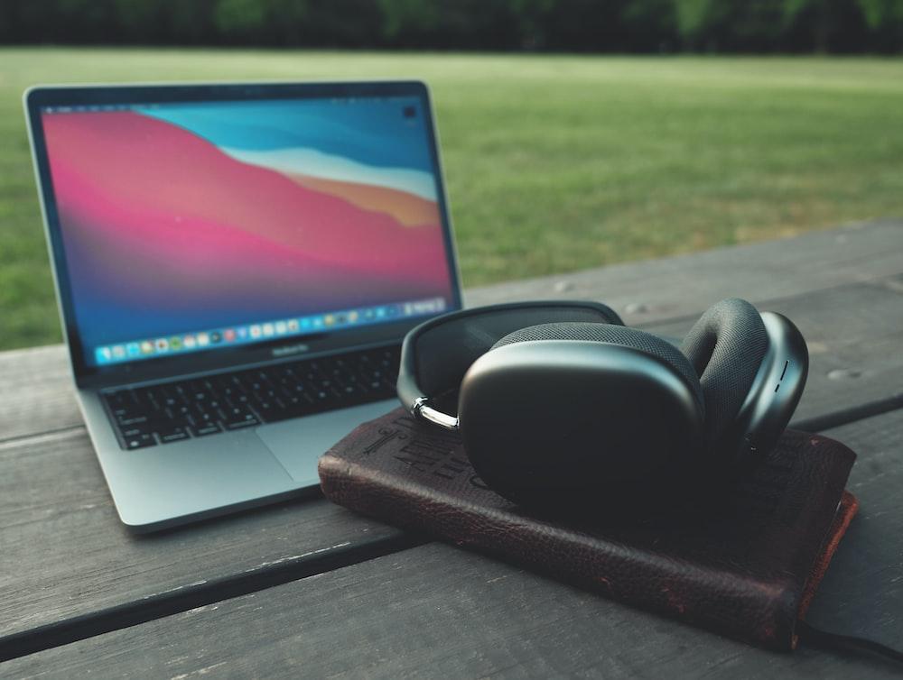 black headphones beside macbook pro