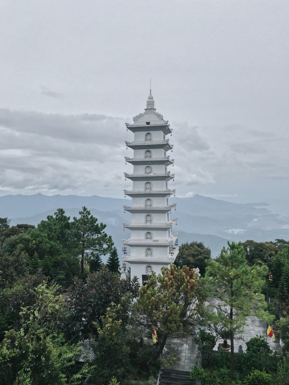 white concrete tower surrounded by green trees under white clouds during daytime