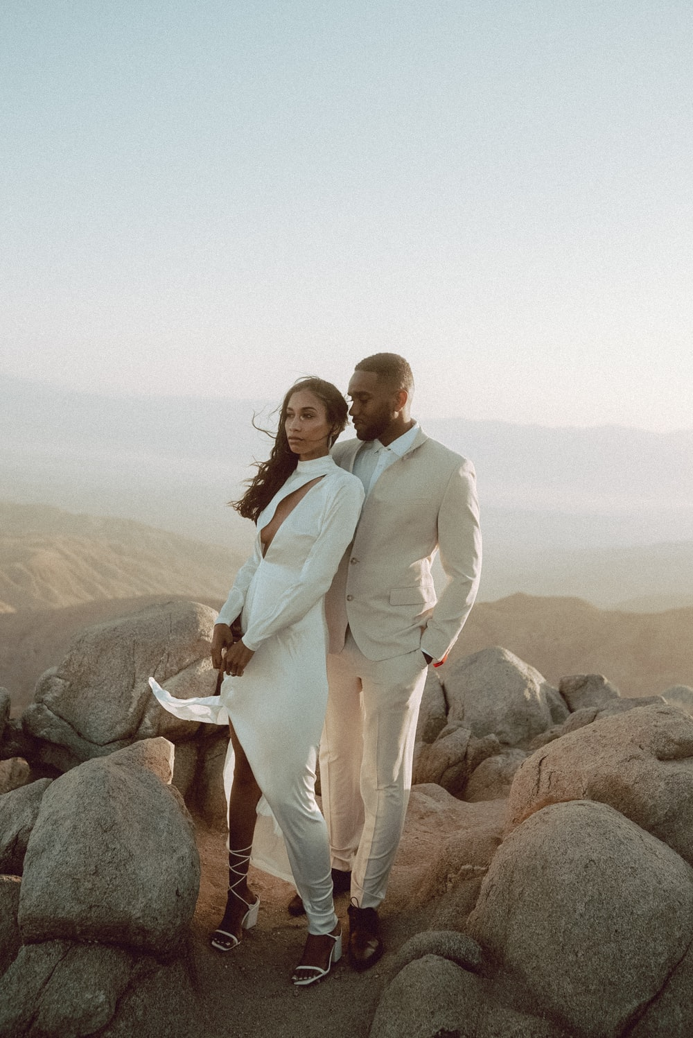man in white suit standing beside woman in white dress on rock during daytime