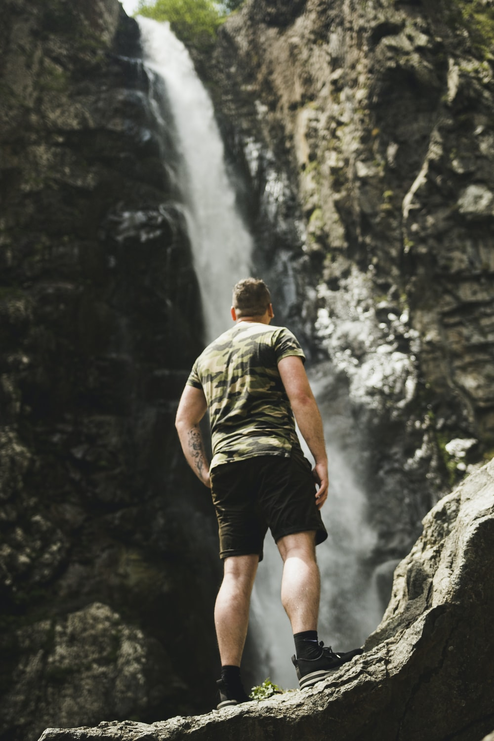 man in green t-shirt and black shorts standing on rocky mountain during daytime