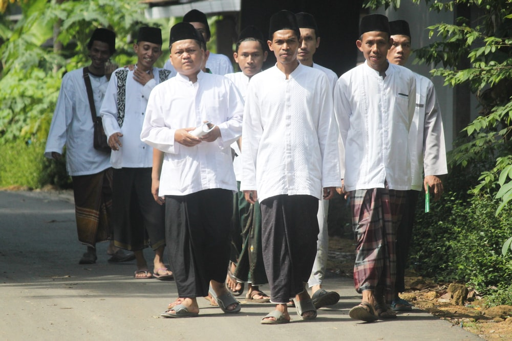 group of men in white dress shirt and black pants standing on gray concrete floor during