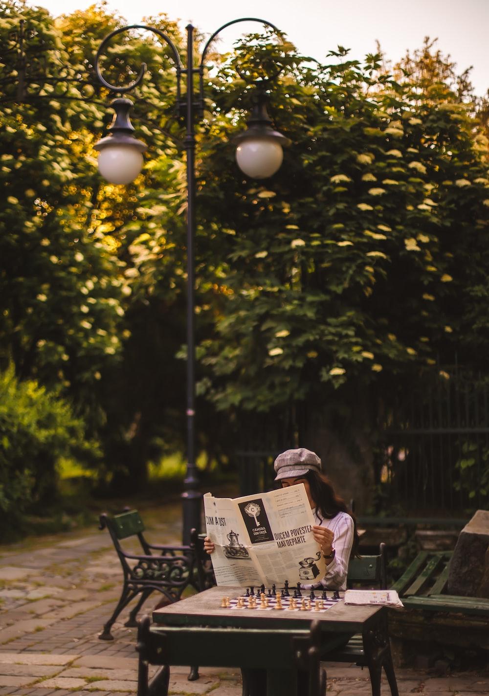 black metal bench near green trees during daytime