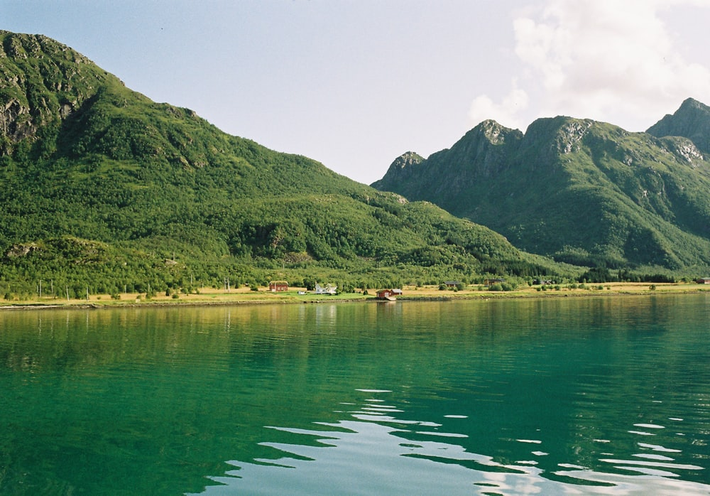 green mountain beside body of water during daytime