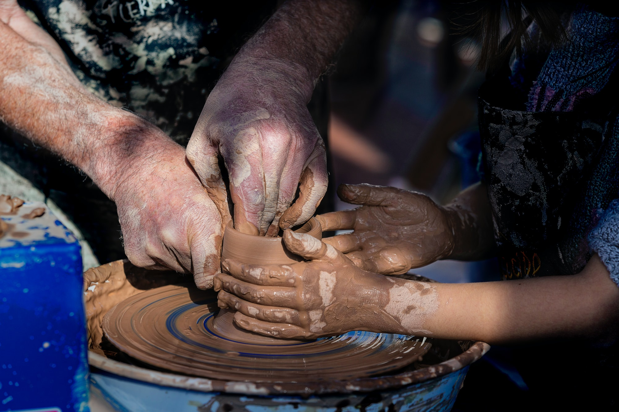 Las manos de un maestro artesano guiando las de un niño para dar forma al barro.