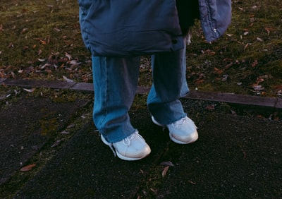 Arad person in blue denim jeans and white sneakers