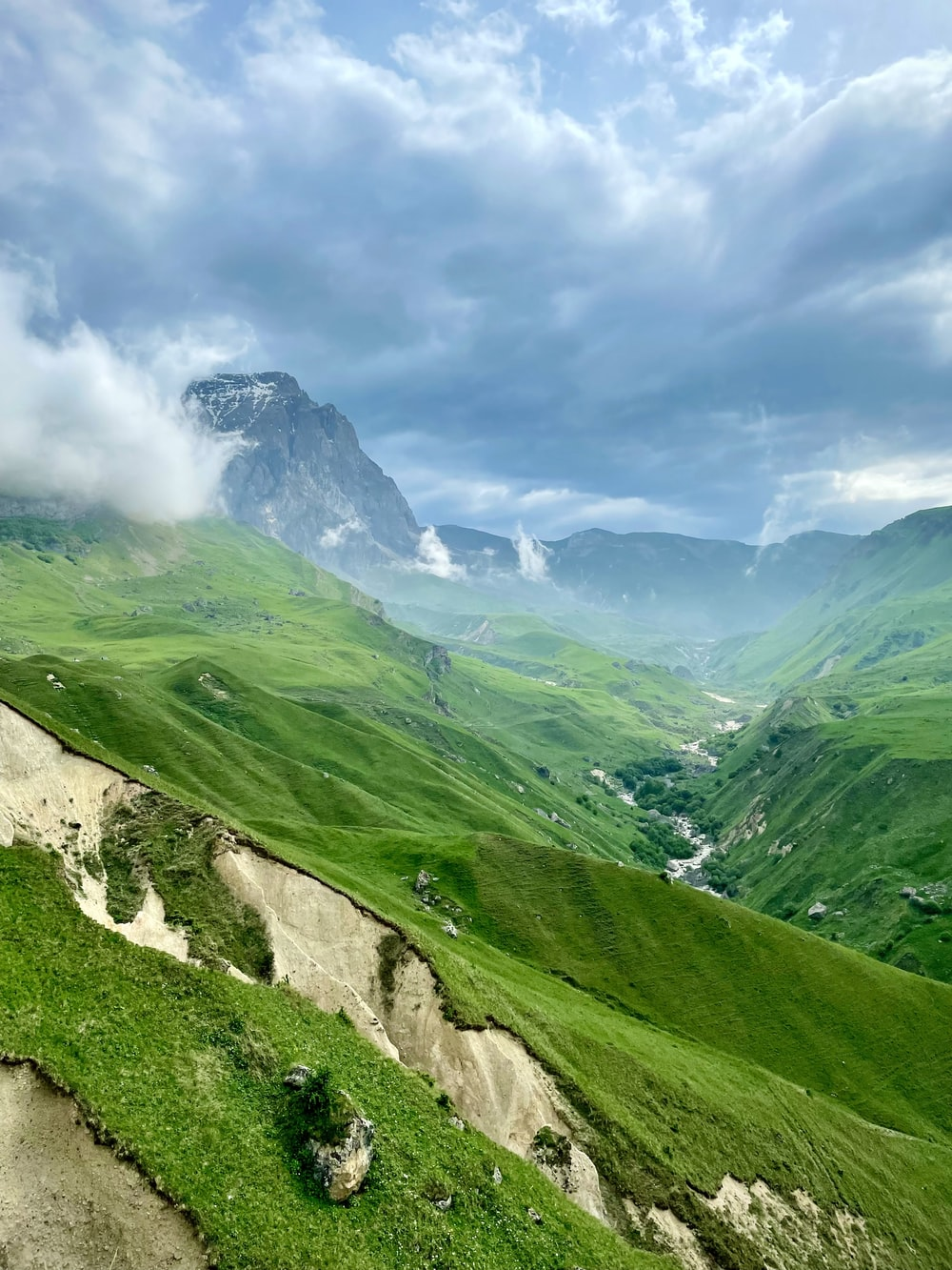 green grass covered mountain under cloudy sky during daytime