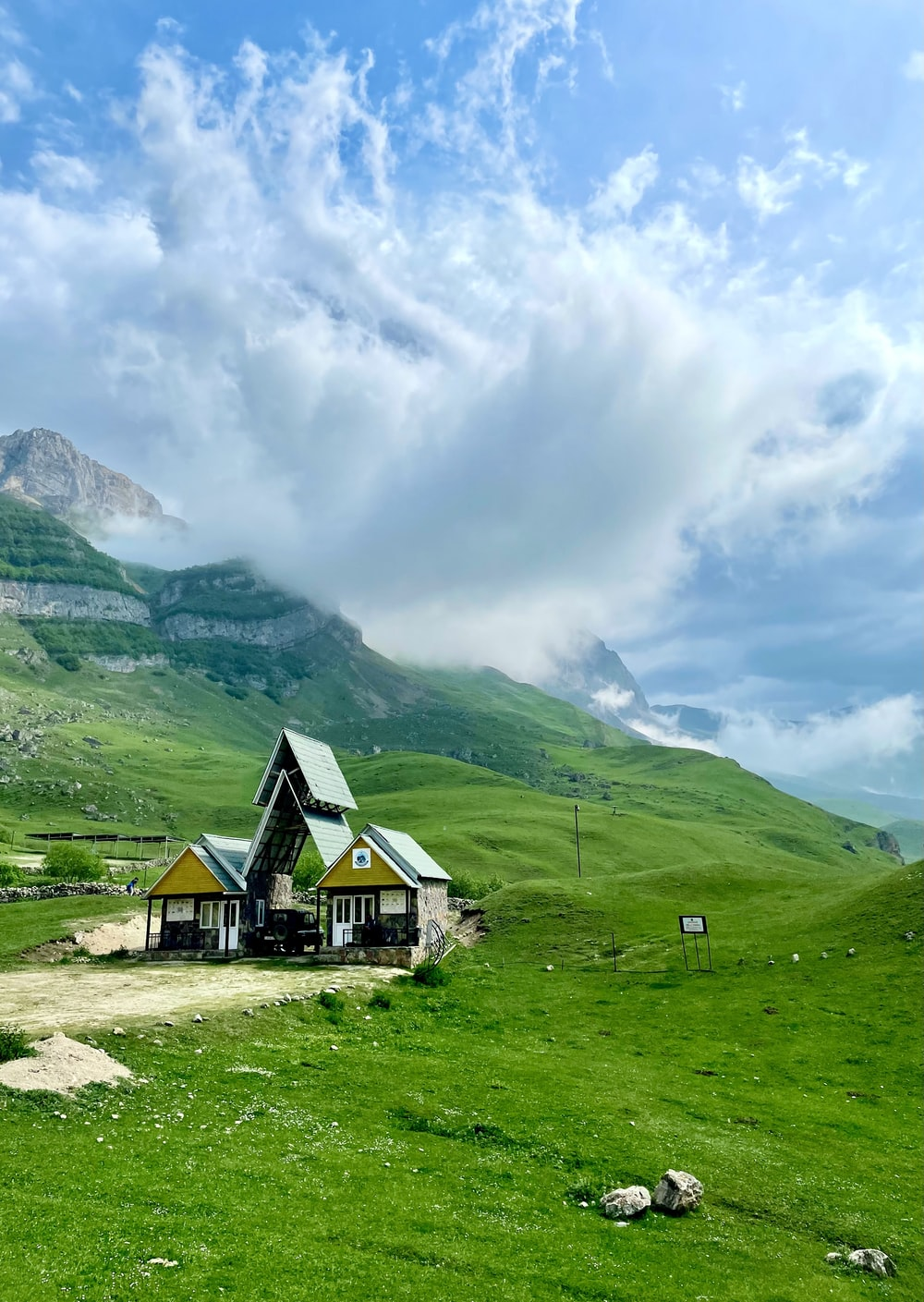 green and brown house near green mountains under white clouds during daytime