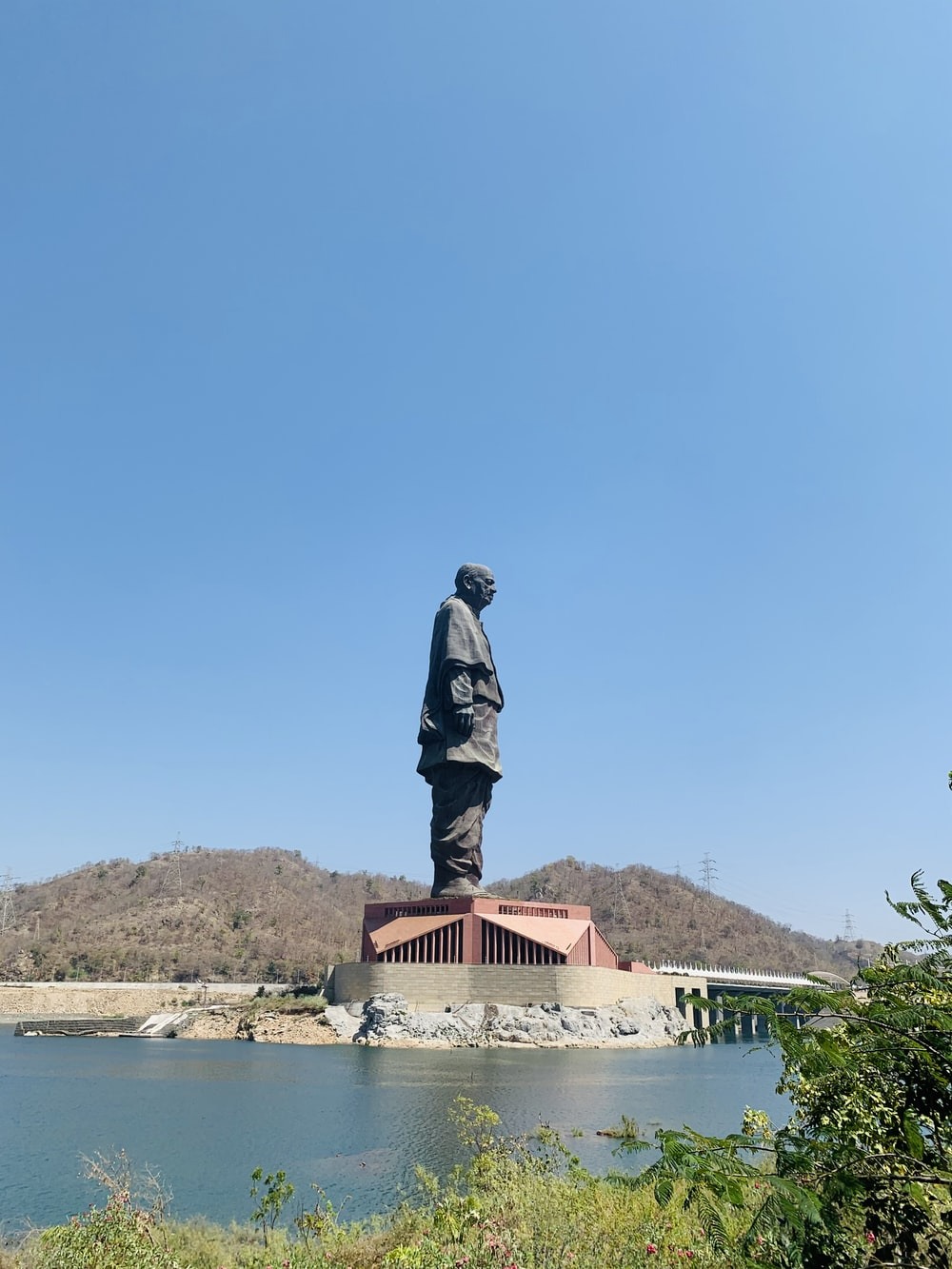 man in black jacket statue near body of water during daytime