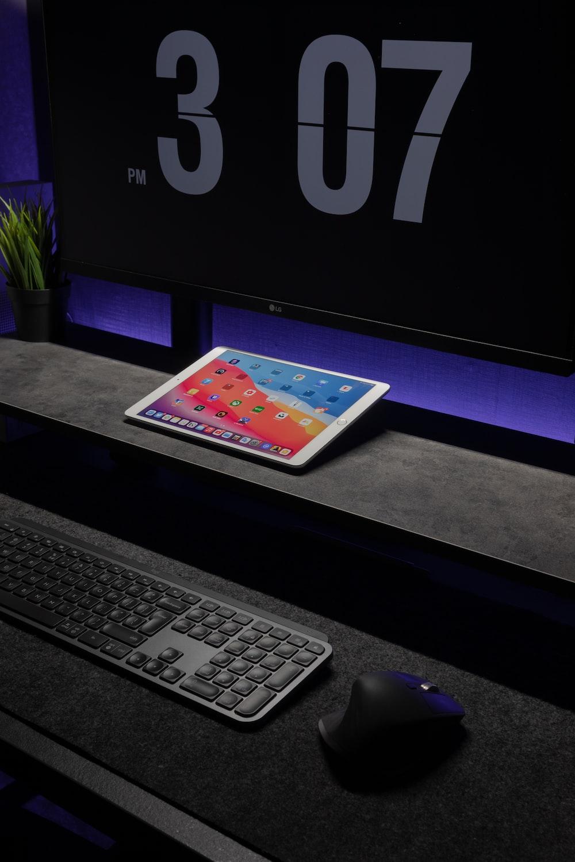 black ipad with keyboard on black table