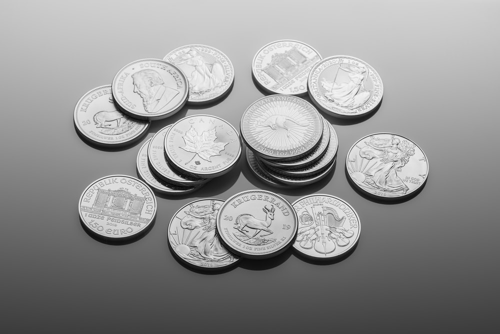 silver round coins on white surface