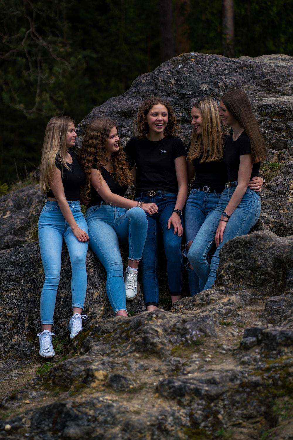 3 women sitting on rock