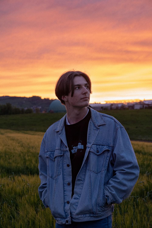 man in blue denim jacket standing on green grass field during sunset
