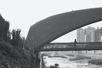 Grayscale photo of bridge over river. Woman crossing bridge, black and white